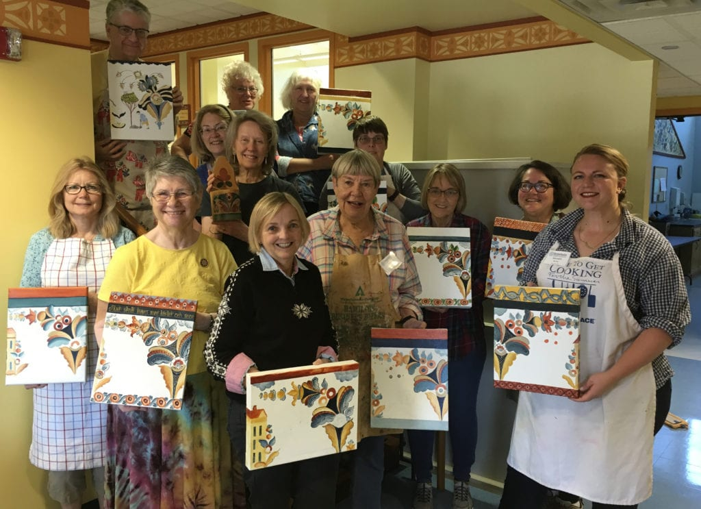 Rosemalers hold up their projects in a Vesterheim Folk Art School class.