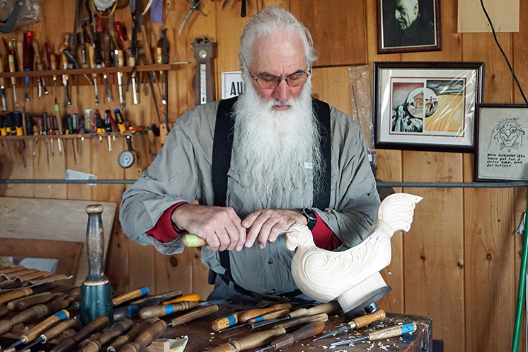 Woodworker Phil Odden carving in his home studio.