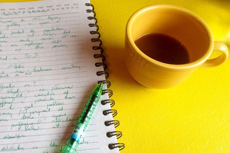 A tabletop with a cup of coffee and a page from the notebook of writer Kathleen Ernst