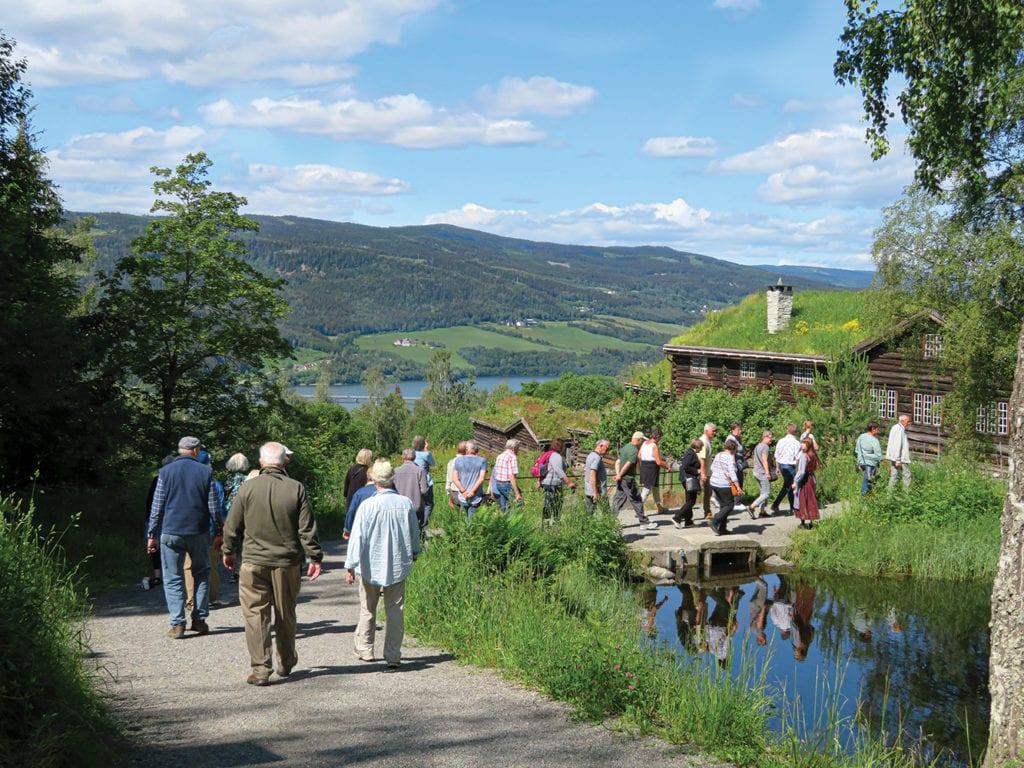 Tour group walks through Maihaugen Museum outdoor area in Norway.