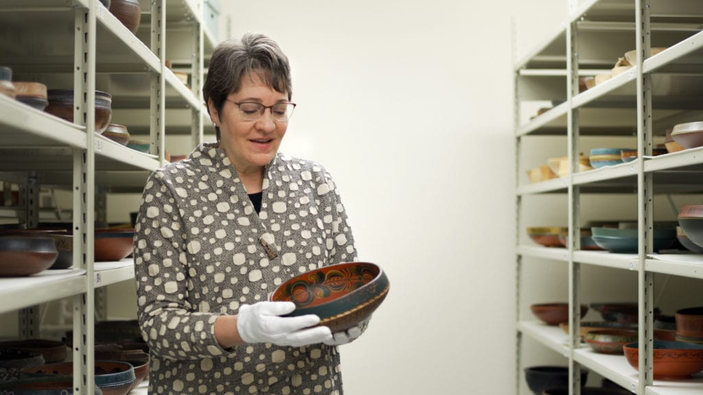 Chief Curator Laurann Gilbertson shows bowl with rosemaling in Vesterheim collection storage.