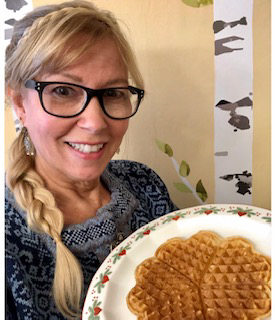 Woman holding plate of waffles