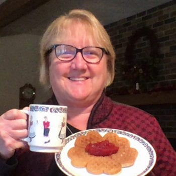 Woman holds plate of waffles and cup of coffee